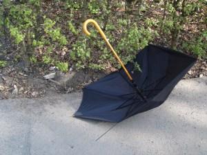 Der Regenschirm, weggeworfen an einer Stelle, an der Kinder täglich unter Polizeischutz auf ihren Schulbus warten.